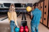 mnohonárodnostní pár s bowlingové koule stojící před uliček v klubu