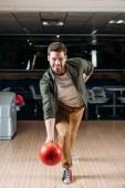 Fotografie šťastný mladý muž vrhací bowlingové koule v klubu