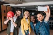 Fotografie Skupina mladých přátel pořizování selfie společně v kuželky
