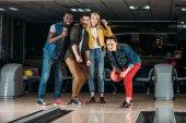 nadšený, skupina mladých přátel hrát bowling společně