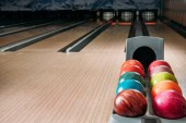 Fotografie stojan s barevnými bowlingové koule v klubu před uličky