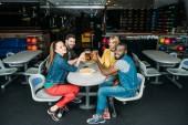 Skupina mladých přátel, cinkání, džbánky piva v bowling Clubu