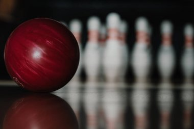 close-up shot of red bowling ball on alley in front of pins