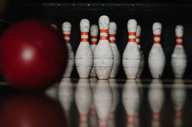 grungy bowling pins with red ball on foreground
