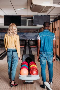 rear view of multiethnic couple standing near stand with balls at bowling club