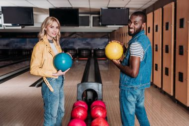 happy multiethnic couple with bowling balls looking at camera at club