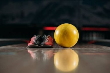 yellow bowling ball with shoes on alley at club