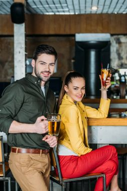 young couple with alcoholic beverages spending time together in bar