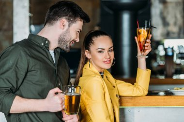 young woman with cocktail looking at camera while man flirting with her in bar