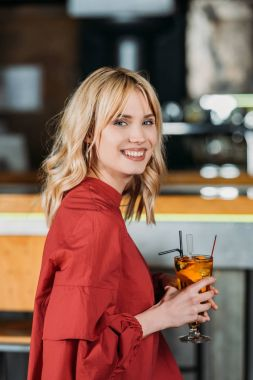 happy young woman with cocktail spending time in bar