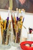 malířské štětce v brýlích na stole v dílně