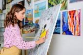 Fotografie Seitenansicht der schönen weiblichen Malerei in der Werkstatt