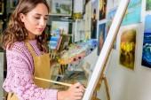Fotografie Seitenansicht der schönen weiblichen Malerei auf Leinwand in der Werkstatt