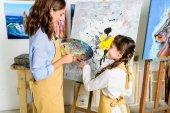 Fotografie Lehrer und Schüler wählen Farbe auf Palette in der Werkstatt der Kunstschule