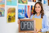 Fotografie happy female artist holding signboard with word open in workshop