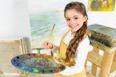 Fotografie Kind hält Pinsel und Palette in der Werkstatt der Kunstschule