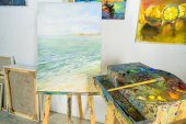 Fotografie canvas on easel and paintings on wall in workshop
