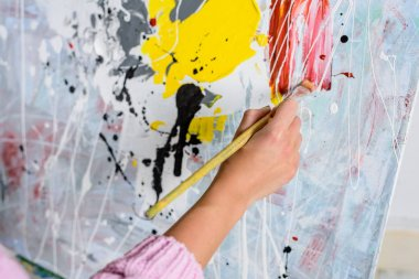 cropped image of female artist painting in workshop