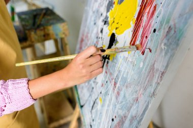 cropped image of female artist painting in workshop with painting brush