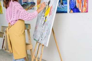cropped image of female artist painting with brush in workshop