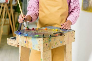 cropped image of female artist applying paints on palette in workshop
