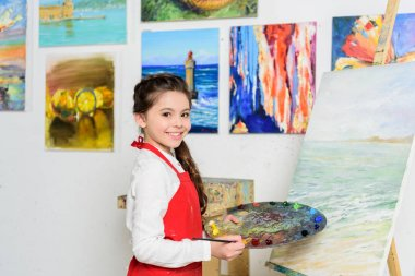 Preteen kid holding palette near canvas in workshop of art school stock vector
