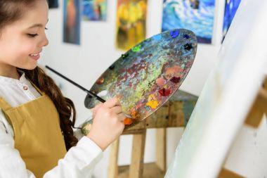 kid taking paint from palette in workshop of art school