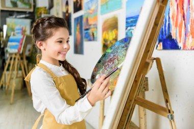 side view of smiling kid painting in workshop of art school