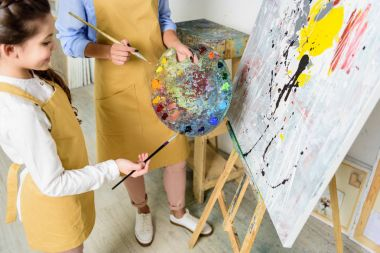 cropped image of teacher and pupil choosing paint on palette in workshop of art school