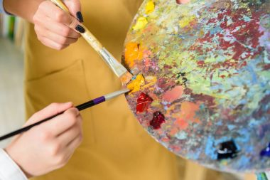 Cropped image of teacher and pupil taking same paint from palette in workshop of art school stock vector