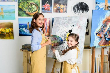 Teacher and pupil standing near canvas in workshop of art school and looking at camera stock vector