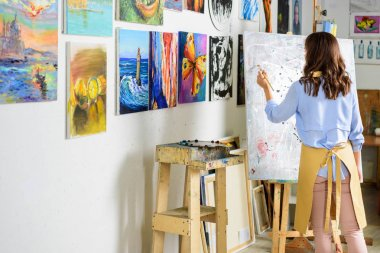 rear view of left-handed female artist painting on canvas in workshop