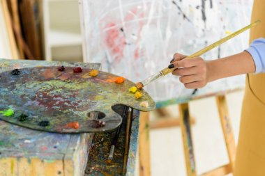 cropped image of left-handed artist taking paint from palette in workshop