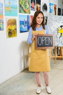 beautiful female artist holding signboard with word open in workshop and looking at camera