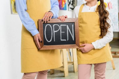 cropped image of teacher and pupil holding signboard with word open in workshop of art school