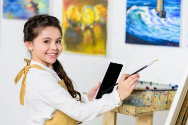 side view of smiling kid painting and using tablet in workshop of art school