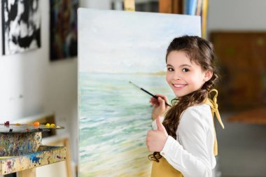 smiling kid painting in workshop of art school and showing thumb up