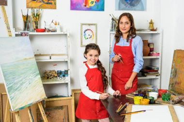 happy teacher and pupil looking at camera in workshop of art school