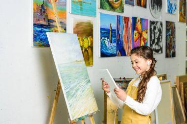 kid using tablet in workshop of art school