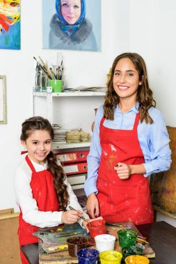 smiling teacher and pupil looking at camera in workshop of art school