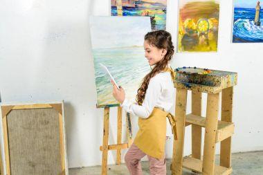 side view of kid using tablet in workshop of art school