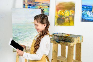 side view of kid looking at tablet in workshop of art school