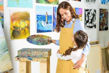 teacher and pupil hugging in workshop of art school