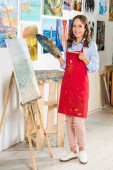 beautiful female artist holding painting brush and palette near canvas in workshop