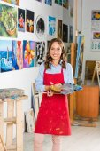 beautiful female artist holding painting brush and palette in workshop
