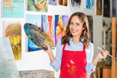 smiling beautiful female artist holding painting brush and palette in workshop