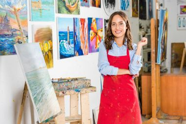 beautiful female artist standing and looking at camera in workshop