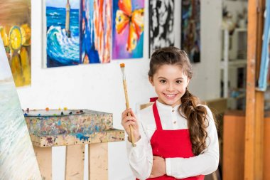 kid holding painting brush and looking at camera in workshop of art school