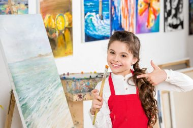 Kid pointing on painting brush in hand in workshop of art school stock vector