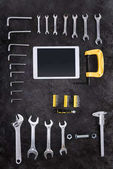 Top view of various construction tools and digital tablet on black